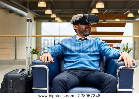 Portrait of mature bearded man wearing VR headset sitting in armchair immersed in game and looking around, copy space