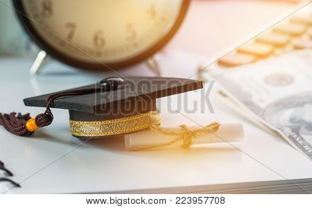 Graduate study international abroad concept, Graduation cap scroll certificate near documents report chart,blur US Dollar. Graduate study abroad program for students foreign, Finance Education Concept