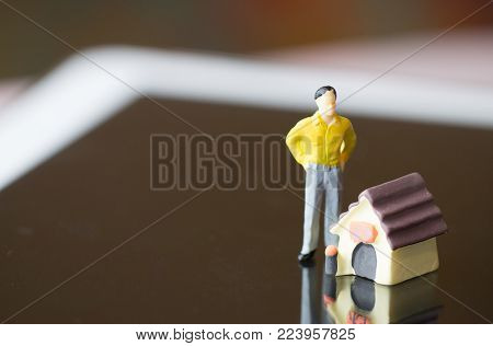 Miniature people yellow suit standing near miniature house with and mini car on Bangkok city map for travel around direction to destination with car dealer, Property real estate investment concept