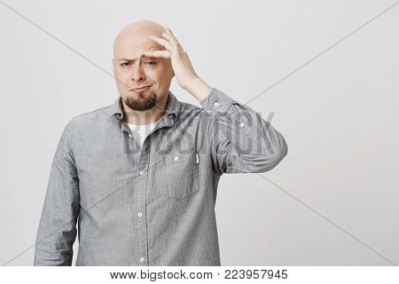 Stressed frustrated caucasian bearded bald male dressed in gray shirt touching his forehead with hand, suffering from pain, being tired and overworked. Hairless man frowning face in irritation and pain