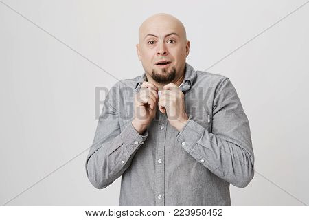 Clueless puzzled bald man with beard and opened mouth, having hesitation, being stunned and confused, expressing uncertainty. Facial expressions, life perception and attitude concept. Hairless man looks at camera in bewilderment