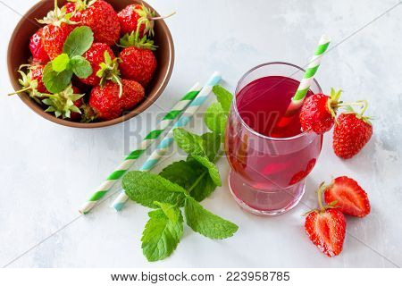 Freshly Squeezed Strawberry Berry Juice And Fresh Strawberry Berries On A Gray Stone Or Slate Backgr