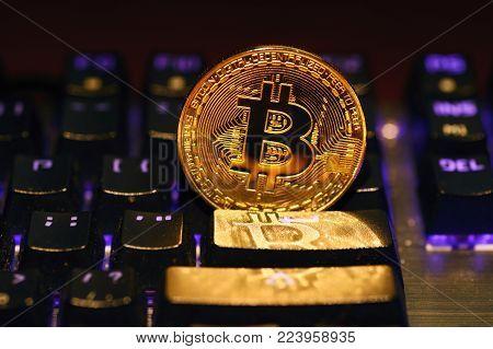 Bitcoin. Crypto currency Bitcoin, BTC, Bit Coin. Macro shot of Bitcoin golden coin on the illuminated keyboard background. Blockchain technology, bitcoin mining concept
