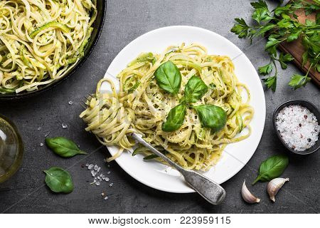 Pasta spaghetti with zucchini, basil, cream and cheese on black stone table. Vegetarian vegetable pasta. Zucchini noodles. Top view.