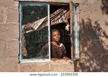 African woman in the window in the village, Botswana
