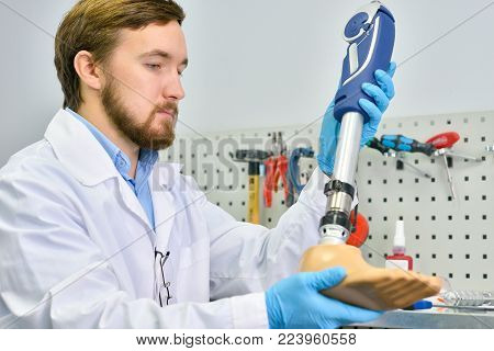 Portrait of young  prosthetist holding prosthetic leg  checking it for quality and making adjustments while working in modern laboratory, copy space