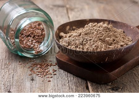 flax flour (gluten-free) in a bowl, flax seeds in a glass jar on an old wooden background