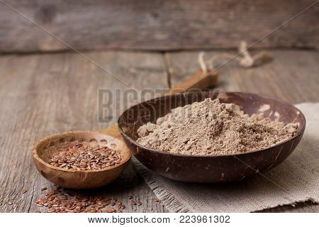 flax flour (gluten-free) in a bowl, flax seeds in a wooden spoon on old wooden background