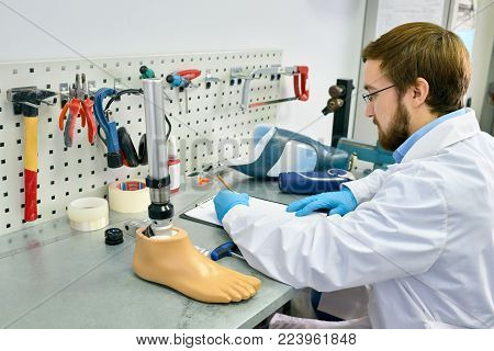 Portrait of  prosthetics technician  making prosthetic leg at desk in office and writing notes, copy space