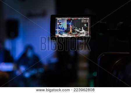 LCD display on the camcorder. Filming of the concert. Musicians playing the double bass, synthesizer, guitar and percussion.