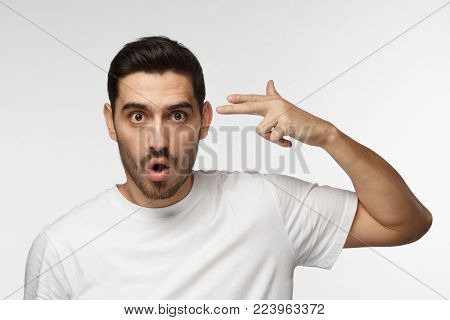 Attractive man having problems, makes suicide gesture, pretends shooting himself, wants to avoid all troubles, isolated on grey background