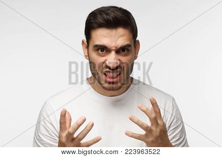 Shut up concept. Mad young man bite his teeth, gesturing with hands. Studio portrait of angry and irritated male in white tshirt yelling, looking crazy and full of anger