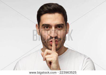 Close up shot of handsome tricky man with shh gesture, asking for silence or to be quiet, isolated on gray background