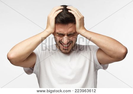 Upset unhappy young man in white t-shirt squeezing head with hands, suffering from headache. People, stress, tension and migraine concept