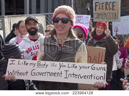 Asheville, North Carolina, USA - January 20, 2018: One young woman, among many marching and carrying signs, holds a sign saying