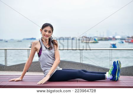 Sports concept. Beautiful girl is exercising on the beach with warm up. Beautiful girl is happy to exercise.  Beautiful girls like to exercise by warm up. People are exercising on the beach.