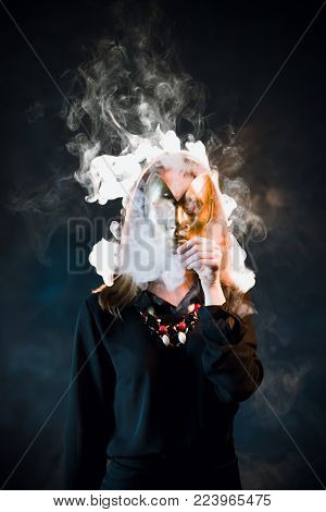 Woman covering her face with a mask surrounded by nicotine fumes. Danger of being passive smoker concept