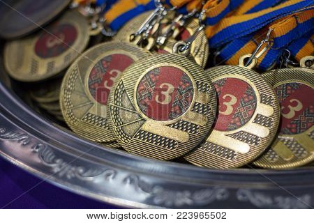 Many bronze medals with copper ribbons and yellow- blue ribbons on a silver tray, Champions awards, achievements in sport, the third place prize for the winner