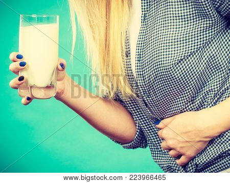 Lactose intolerance, health problem with dairy food products concept. Woman holding glass of milk having bad stomach ache.