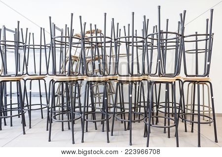 in a classroom, there are metal stacked chairs on top of each other