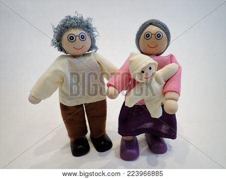 Baby with two grey haired grandparent dolls