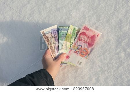 A man's hand reaches for a bundle of Chinese money in the snow. Banknotes of one hundreds, twenty and ten RMB. Nice prize