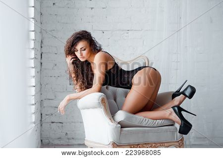 Perfect, sexy body, legs and ass of young woman on high heels wearing seductive black lingerie. Beautiful hot female in lacy bodysuit posing on luxury vintage chair