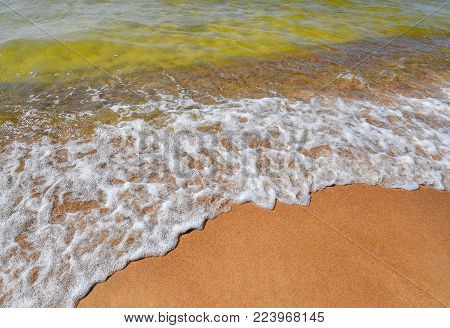 Sea, sand and summer. Beautiful transparent water waves and soft sand on the beach. Seacoast. Water's edge
