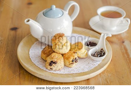English breakfast and tea break, scones on wooden table with a cup of tea.