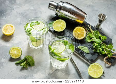 Mojito cocktail with lime and mint in highball glass on a stone table. Drink making tools and ingredients for cocktail.