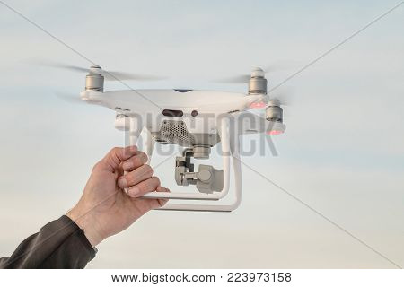 The hand holds white dron at landing. Landing a droned hand with spinning propellers. Flying drone on the sky.