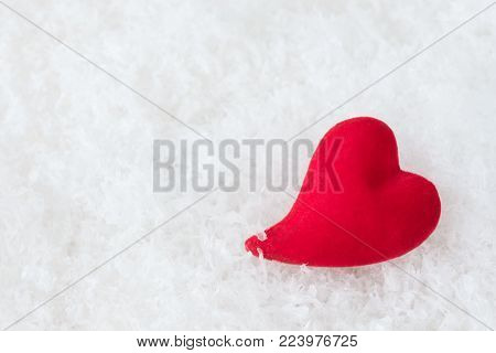 Single red heart lie on white fluffy cold snow. Metaphor of love ore loneliness. Greeting card for Valentine's Day