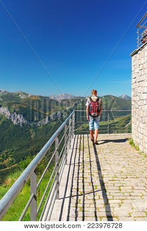 FUENTE DE,SPAIN - JULY 10, 2016: The tourist on the observation deck at mountain top. The young man with a backpack, the rear view