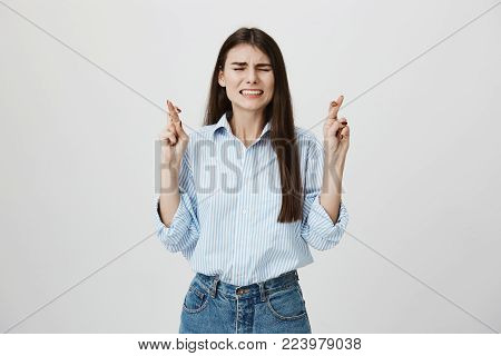 Indoor portait of cute caucasian student, raising hands and crossing fingers with closed eyes and worried expression, showing her desire for something to happen, standing over gray background. Emotions cocnept.