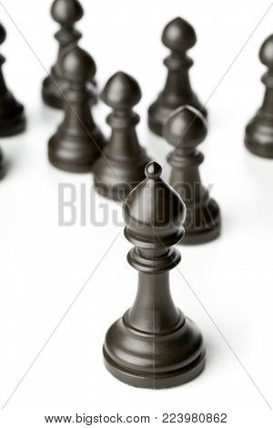 King chess figure in front of pawn chess figures - management, leadership, teamlead or strategy concept over white background