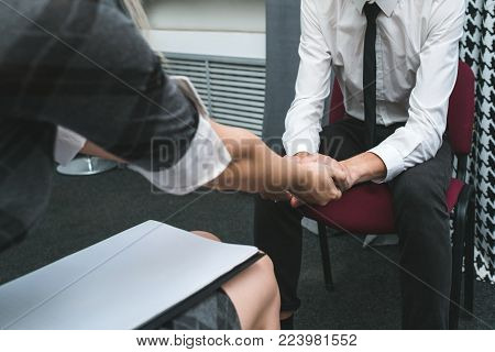 love affair at work between man and woman. support each other. hold hands. office romance