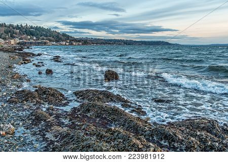 A view of the shoreline at low tide in West Seattle, Washington. It is a stormy day.