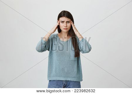 Stressed frustrated dark-haired young female dressed in blue sweater and jeans holds hands on temples, suffers from headache, feels annoyed and bored because of noise and useless information