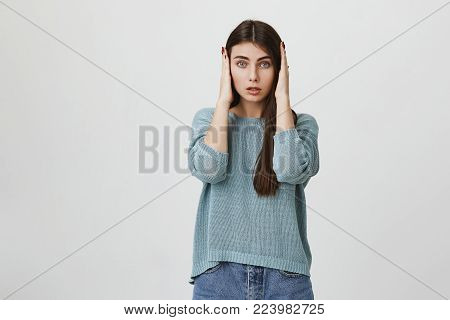 Beautiful young female with long dark hair in casual clothes being troubled to listen advices of parents isolated against blank wall background. European student girl closing ears with hands