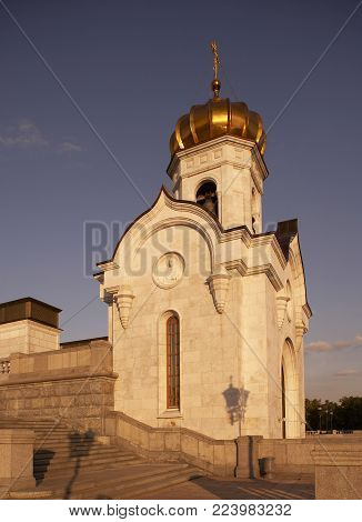 GOLD DOME AND CRUCIFIX ON BELL TOWER AT ENTRANCE TO CATHEDRAL OF CHRIST THE SAVIOUR AT TWILIGHT MOSCOW RUSSIA