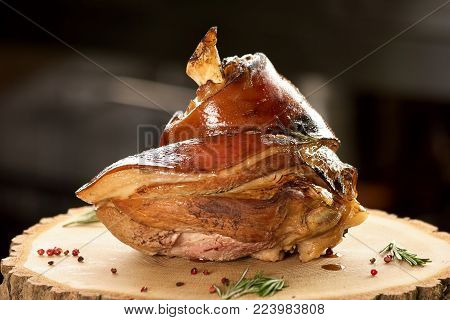 Pork knuckle on wooden surface. Horisontal pork knuckle on round wooden table with side dish, close-up.