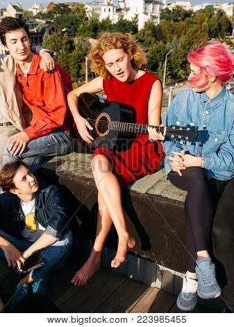 Barefoot young girl busker singing and playing the guitar at a rooftop. Artistic musician lifestyle. Teenagers leisure
