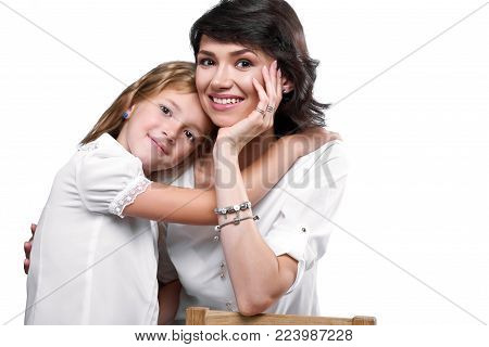 Studio close-up of a beatiful couple: mother and daughter, who huggs her. They look very happy, smiling and wear white t-shirts. Photo was made on white studio background.