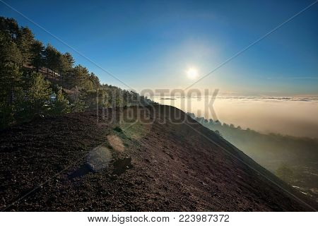 volcanic ashes of Mezza Luna crater and low clouds at sunset in Etna Park, Sicily (lens flare)