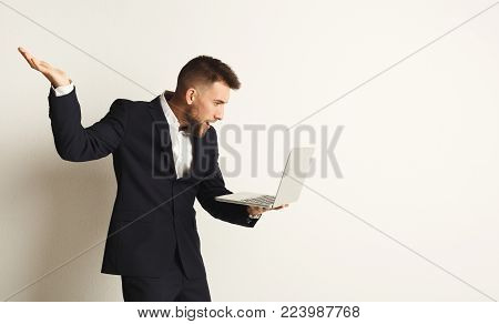 Surprised young caucasian businessman posing in studio and using laptop on white background. Confident man in formal clothes, copy space