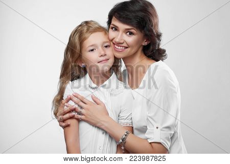 Close-up of wonderful family couple: beatiful mother and her little nice daughter. They are very happy with pretty smiles. They wear white t-shirts. Photo was made on the white studio background.