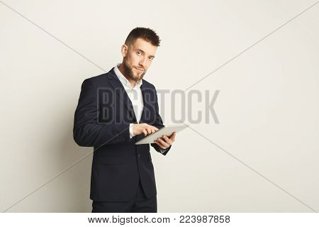 Handsome young caucasian businessman posing in studio and using digital tablet, typing, surfing the internet on white background. Confident serious man in formal clothes, copy space, isolated