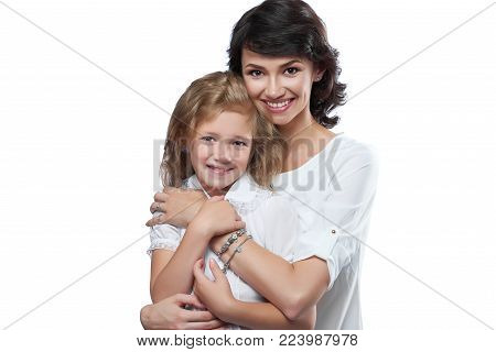 Close-up of nice family couple: beatiful mother and her little nice daughter. They are very happy with pretty smiles. They wear white t-shirts. Photo was made on the white studio background.