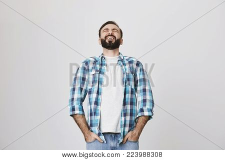 Studio shot of handsome european adult with beard and moustache, laughing out loud, stooped back, holding hands in pockets of jeans, over gray background. Guy watches stand up show on TV. Advertisement concept