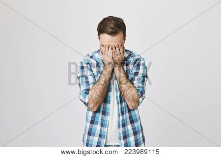 Portrait of miserable and sad male adult, covering face with hands, expressing panic and depression over gray background. Man is frustrated and do not know what to do with his marriage.
